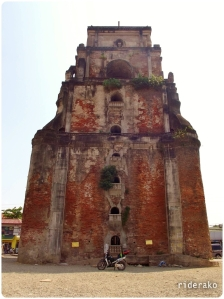 Dhona at the foot of the gigantic Sinking Bell Tower